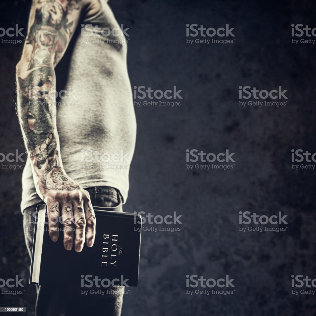 Bible in Arms of Tattooed Man royalty-free stock photo