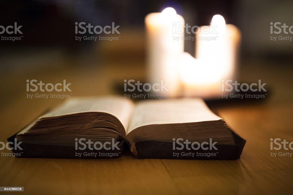Biblia sobre piso de madera, velas encendidas en el fondo - foto de stock