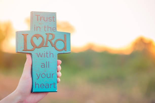 bibel-schriftzug auf blau holzkreuz. vertrauen sie dem herrn von ganzem herzen. - psalm stock-fotos und bilder