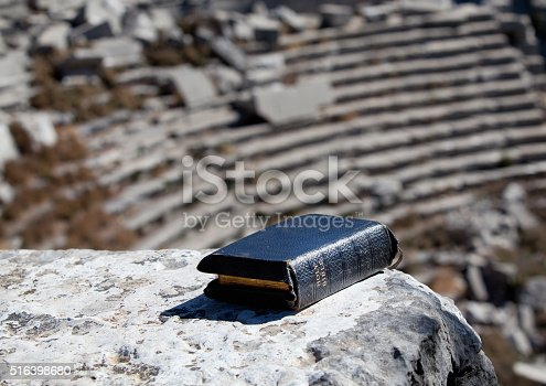 Bible on stairs of antique theatre.The seats of theatre are seen on the background.No people are seen in frame.Shot with a full frame DSLR camera in outdoor.