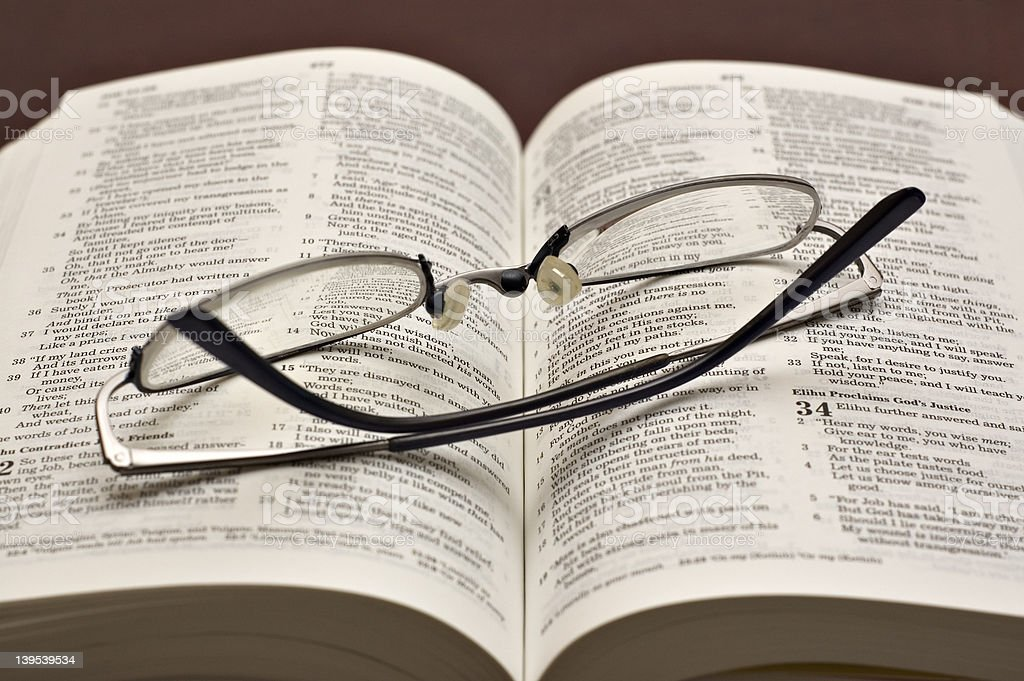 Bible opened with reading glasses stock photo