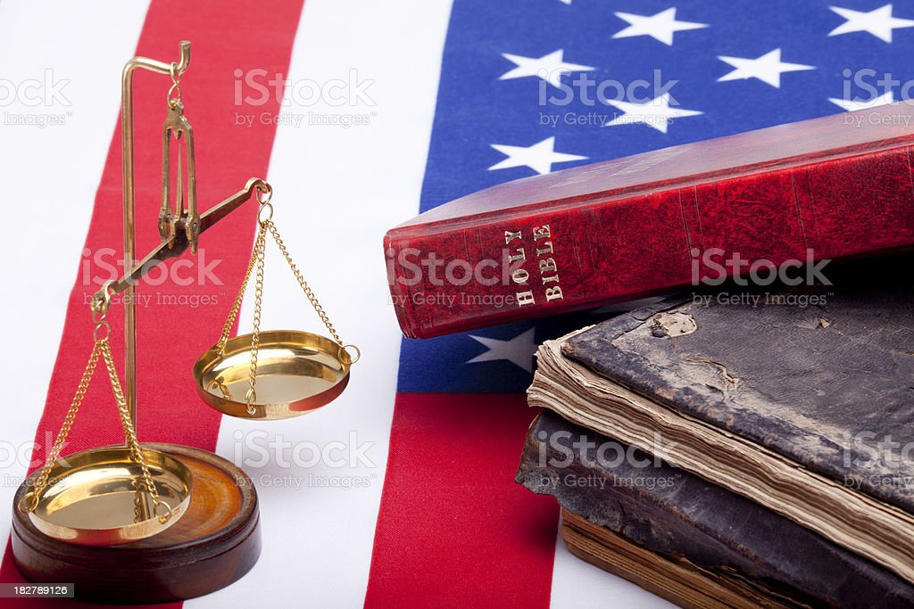 Bible, scales of justice and law books on American Flag stock photo