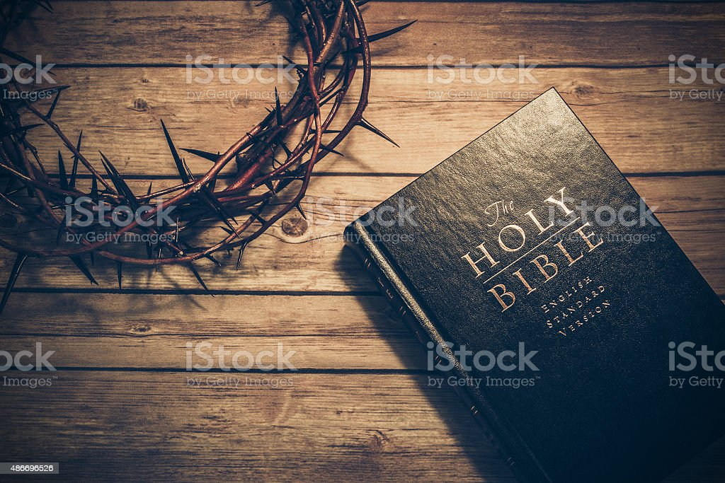 Bible with a crown of thorns on a wooden table stock photo