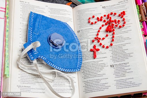 bible with blue mask and red rosary a lot of faith and protection against the corona virus in Brazil