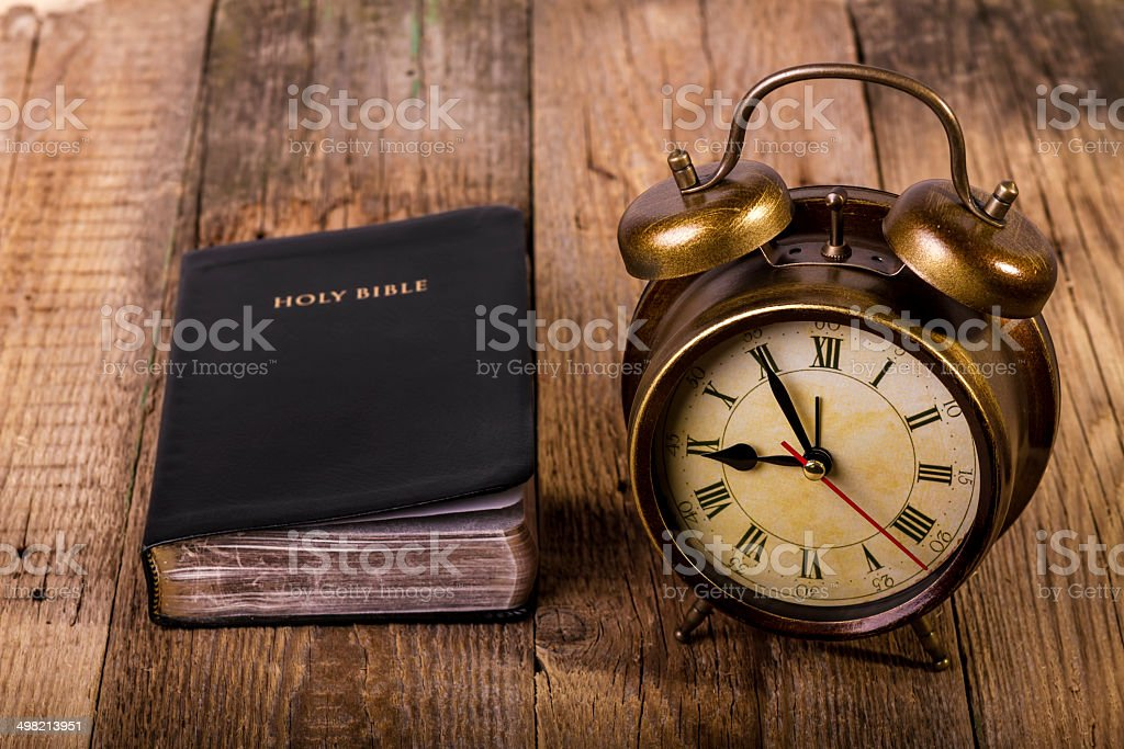 Bible with clock on wood stock photo