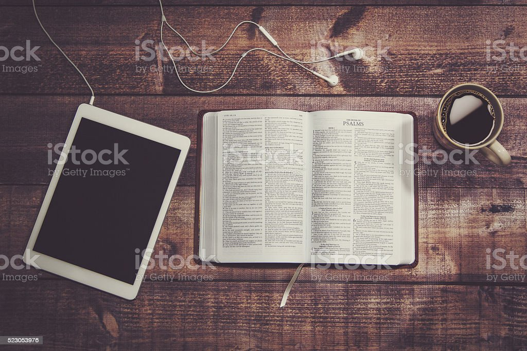 Bible with tablet and coffee in a wooded table.​​​ foto