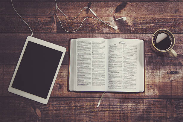 Bible with tablet and coffee in a wooded table. stock photo