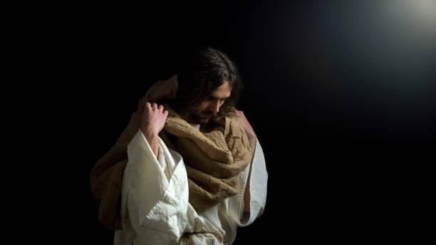 biblical prophet with lowered head standing in darkness, spiritual confession - jesus cristo imagens e fotografias de stock