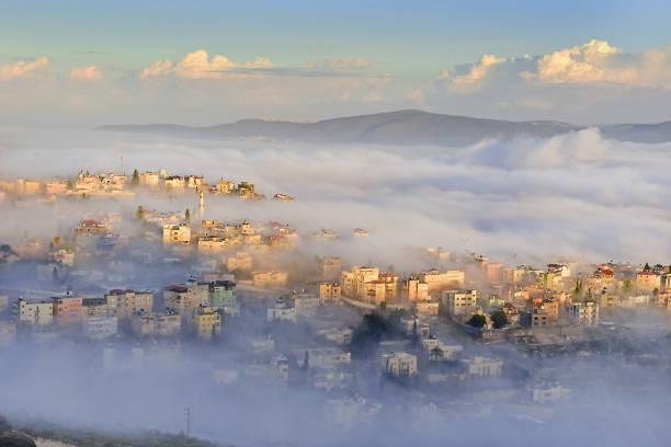 bíblica aldeia de caná da galileia (kafr kanna) em nazaré, em israel, na névoa da manhã - israel - fotografias e filmes do acervo