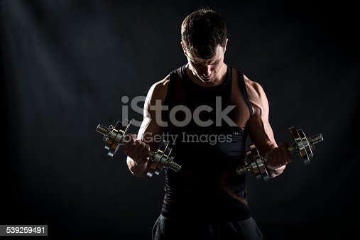 Muscular young man doing exercises for biceps muscles with dumbbells on black background. Looking down.