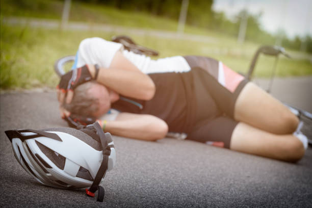 bicycle accident, cyclist lying on the road - head injury stock photos and pictures