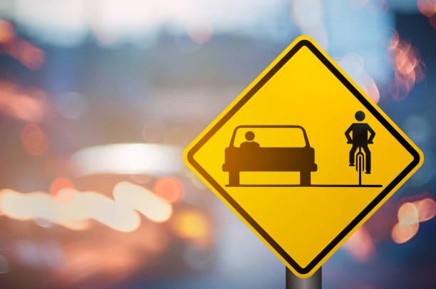 La bicicleta y el coche comparten la señal de advertencia en la carretera del tráfico borroso con colorido fondo abstracto de luz bokeh. Copiar el espacio de transporte y el concepto de viaje. Estilo de color de filtro de tono vintage. - foto de stock