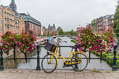 Bicycle and Flowers on a Bridge in Amsterdam Netherlands Canal on a Summer Day