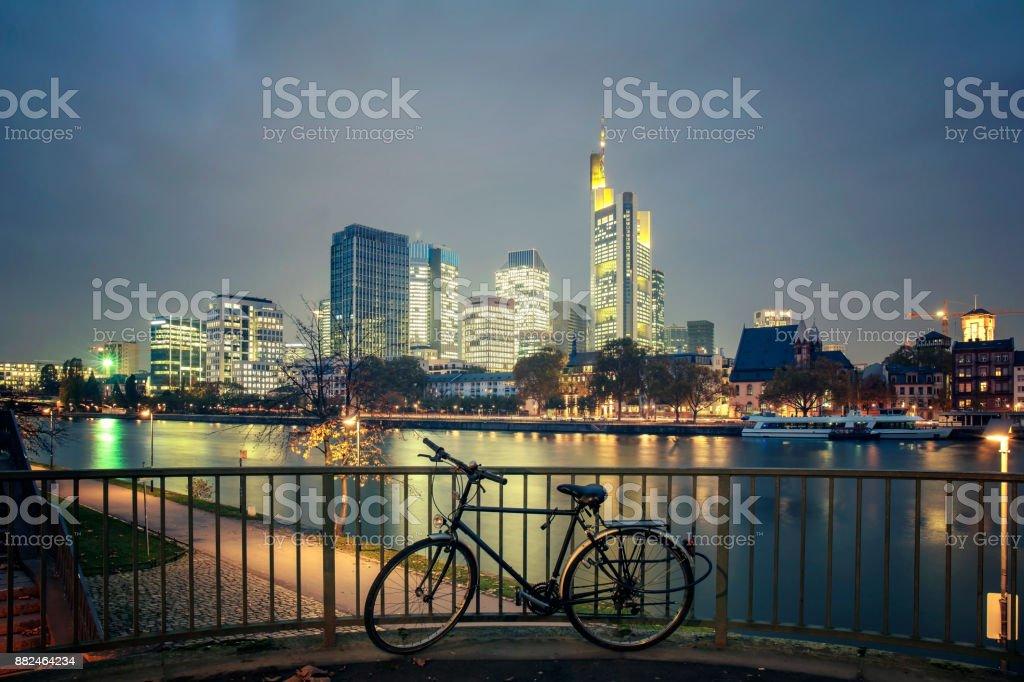 Bicycle and the illuminated Frankfurt am Main skyline at dusk stock photo