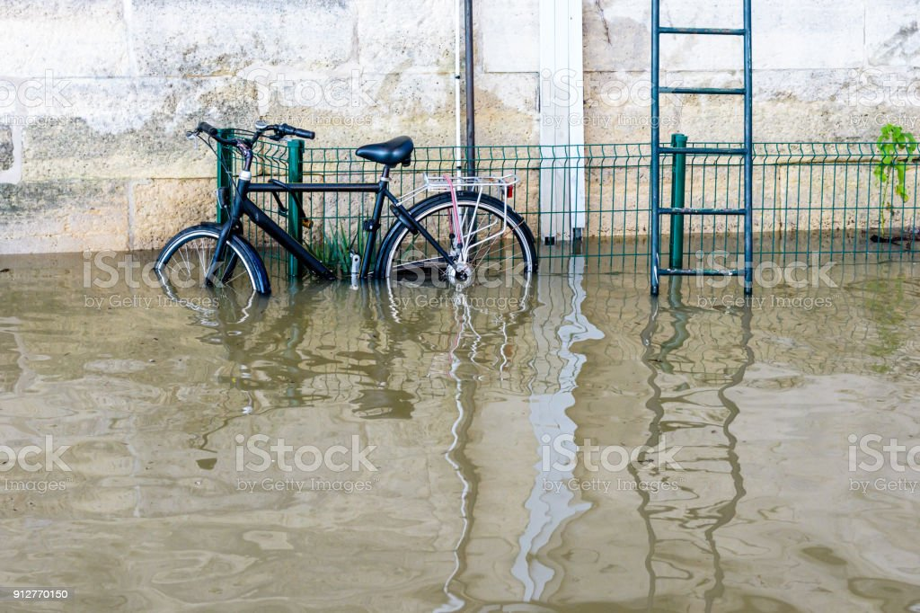 A bicycle attached with a U-lock to a grid, next to a metallic escape ladder, on the riverbanks of the Seine with water at mid-height after the swollen river bursts its banks during a winter flood stock photo