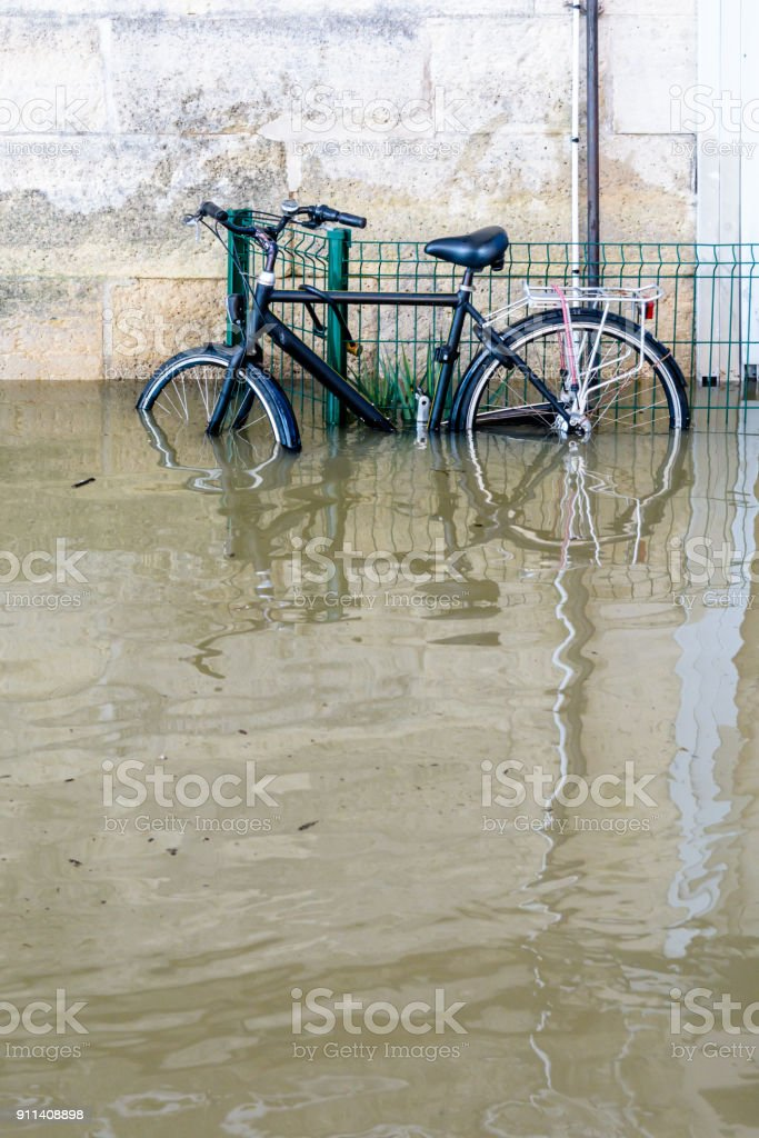 A bicycle attached with a U-lock to a grid on the riverbanks of the Seine with water at mid-height after the swollen river bursts its banks during a winter flood stock photo