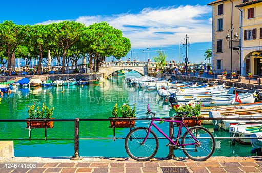 Bicycle bike near fence of old harbour Porto Vecchio with motor boats on turquoise water and Venetian bridge in historical centre of Desenzano del Garda town, blue sky, Lombardy, Northern Italy