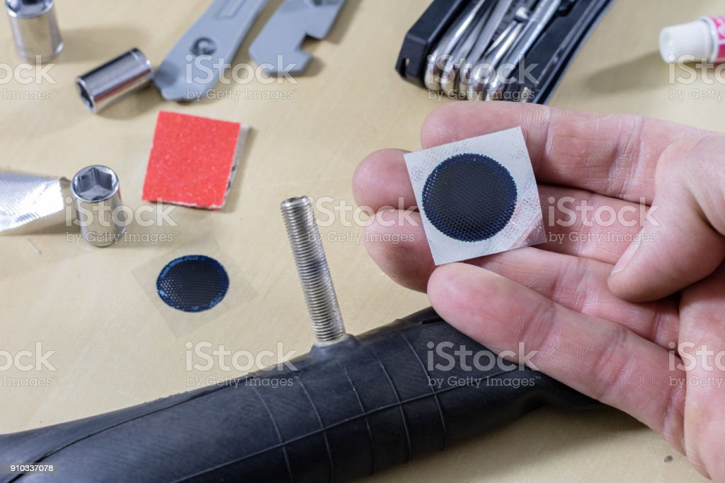 Bicycle breakdown during the trip. Sticking a bicycle tube in a workshop. Mechanic fixing a bicycle tube. Workshop table and tools. stock photo