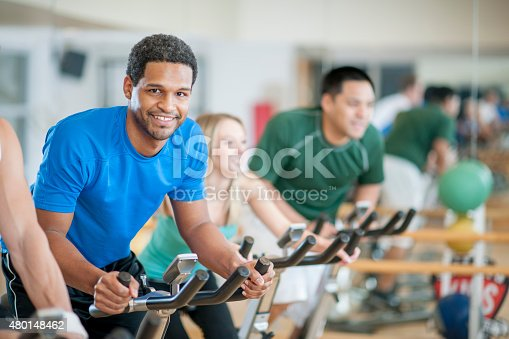A group of young adults doing aerobic exercise in a bicycle exercising class.
