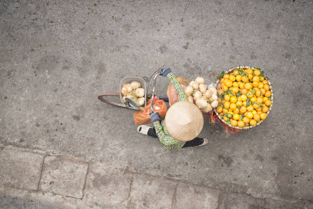 Bicycle Fruit Push Cart, Street Market Life, Old Quarter, Ha Noi, Vietnam Woman pushing her bicycle loaded with fresh fruits at the famous Old Quarter in downtown Ha Noi, Vietnam. Everyday Street Life. hanoi stock pictures, royalty-free photos & images