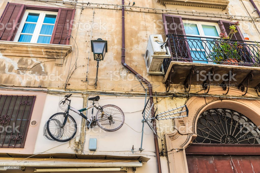 Bicycle hanging on an old wall in Palermo, Sicily, Italy stock photo