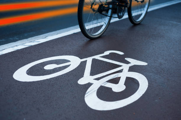 Bicycle in bike lane and traffic, evening - foto stock