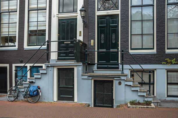 fahrrad vor treppen zu eingangstüren der eleganten gebäude in amsterdam. - wandleuchte treppenhaus stock-fotos und bilder