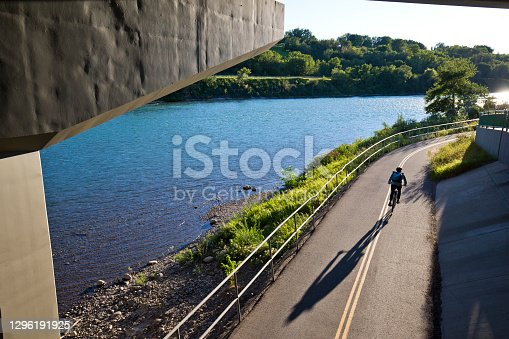 A male bicycle commuter in a large city rides under a bridge in a designated bicycle lane on his way home from work. He rides a one-speed or fixed-gear bicycle. He wears casual clothing, a cycling helmet and, carries a bike messenger style backpack.