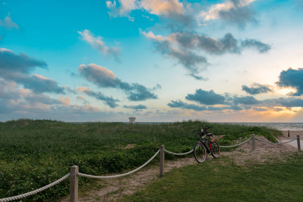 bicycle leaning on a post by the grassy sand dunes  of the beach at sunrise stock photo