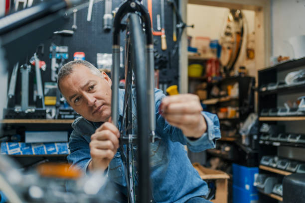 Bicycle mechanic in a workshop in the repair process Service for bike with adept repairing bike. Bicycle mechanic in a workshop in the repair process. Stylish bicycle mechanic doing his professional work in workshop. bicycle shop stock pictures, royalty-free photos & images