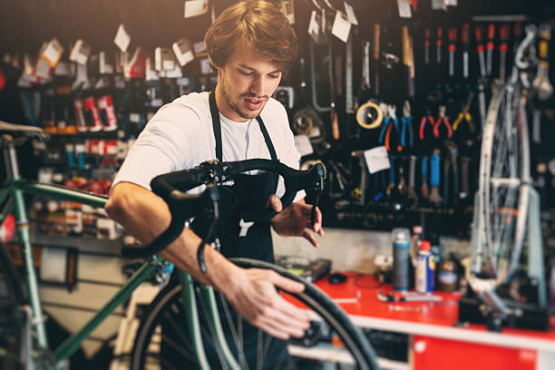 Bicycle Mechanic Handsome young bicycle mechanic focusing on a detail while working on a customer's bicycle bicycle shop stock pictures, royalty-free photos & images