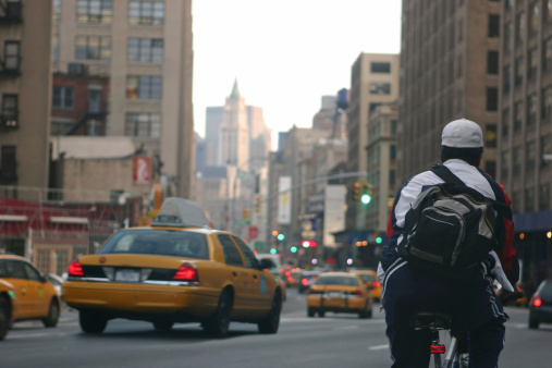 Bicycle messenger in busy downtown New York City street/avenue.