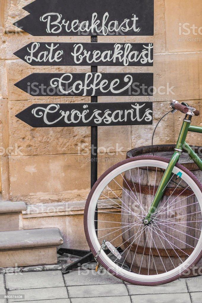 Bicicleta perto de um barril de madeira e ponteiros no qual está escrito café da manhã, café, croissants - foto de acervo