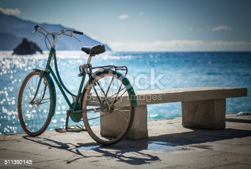 Bicycle near bench against sea.