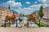 istock Bicycle on a Bridge over a Canal in Amsterdam Netherlands with Blue Sky 1207544710