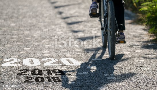 619522908istockphoto Bicycle on asphalt road. New Year 2020 concept 1189346572