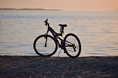Bicycle on beach at sunset