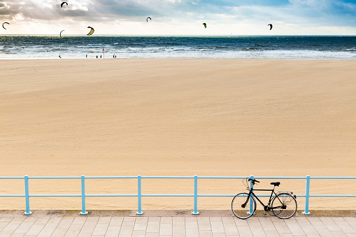 Bicycle on promenade at Scheveningen beach and kiteboarders in the sea on background, in Hague, Netherlands