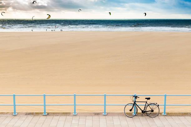 fiets op de promenade bij het strand van scheveningen en kiteboarders in de zee op de achtergrond, in den haag, nederland - den haag stockfoto's en -beelden
