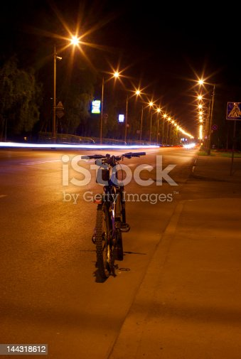 929609038istockphoto bicycle on the night road 144318612