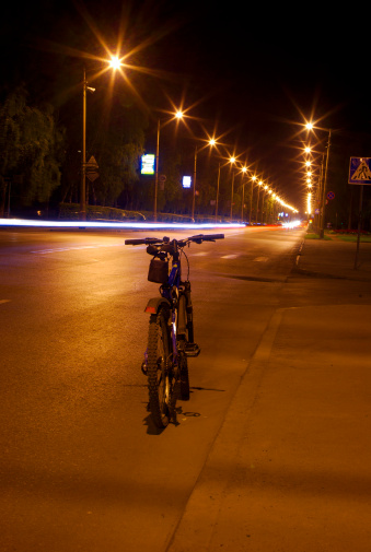929609038 istock photo bicycle on the night road 144318612