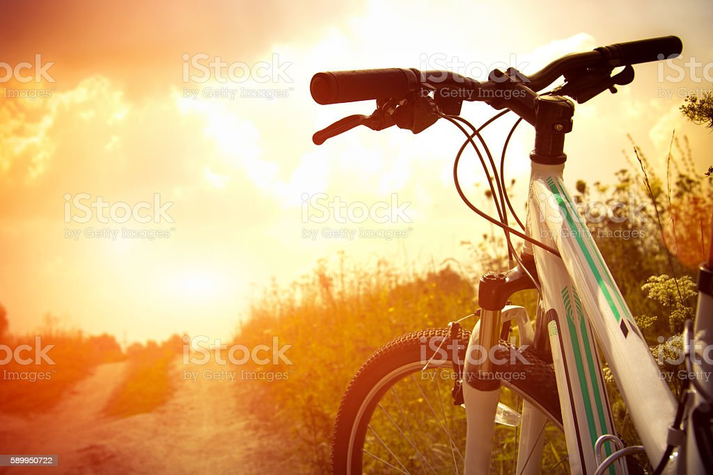 Bicycle on the road Bicycle on the road at sunset Backgrounds Stock Photo