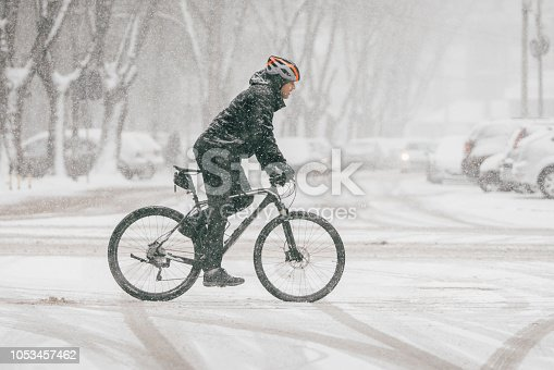 Man riding a bike through the city on the snowy weather
