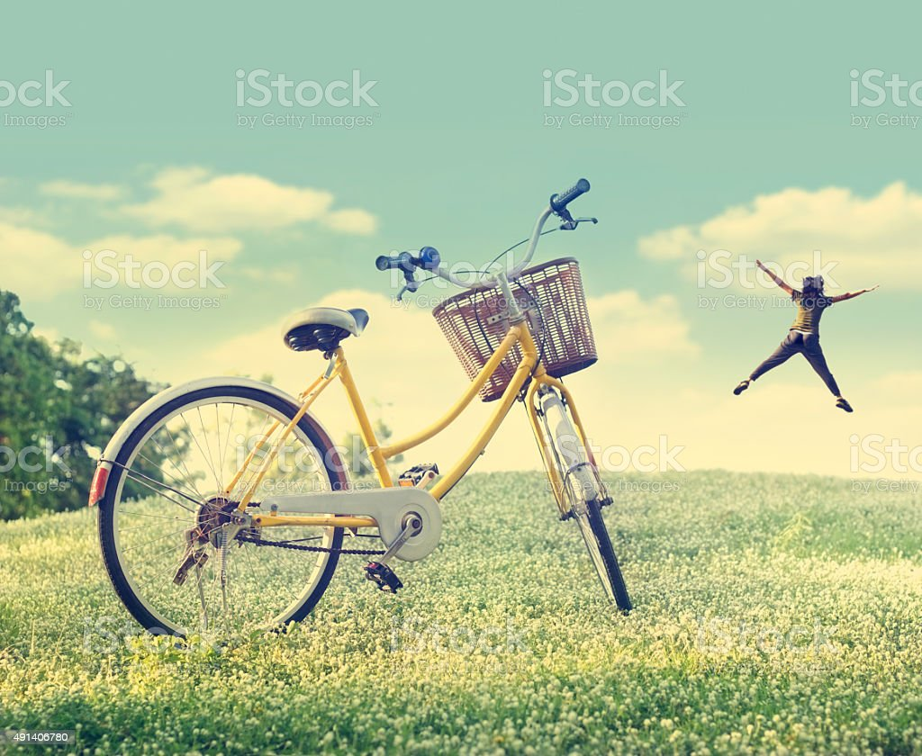 Bicycle on the white flower field and grass in sunshine