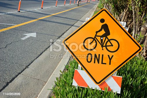 Side of the road has bicycle lane mark and cone off to oncoming cars. This Bicycle sign is also on side of the road for communication awareness and traffic management in Los Angeles.