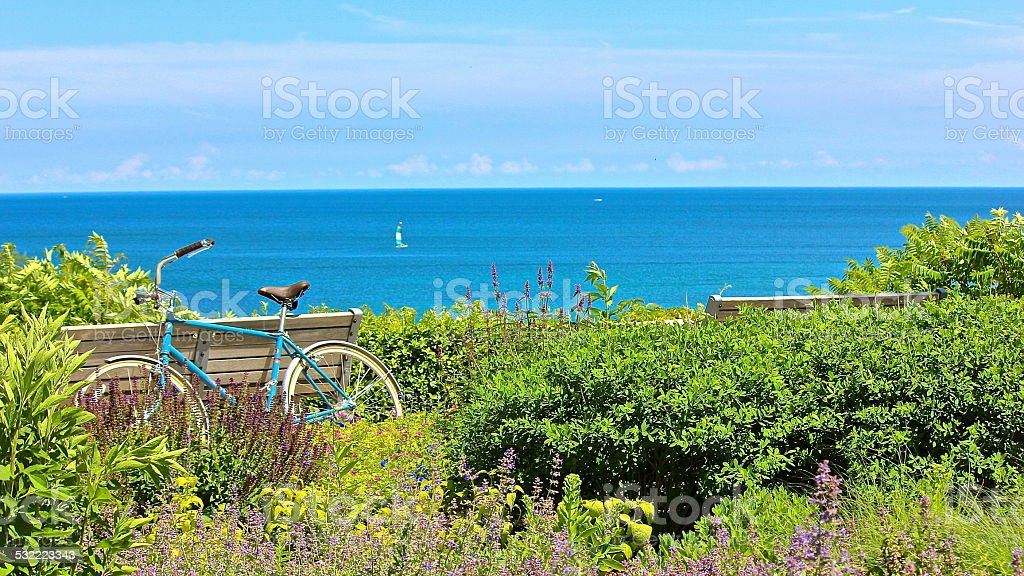 Bicycle, park benches and flowers overlooking lake stock photo