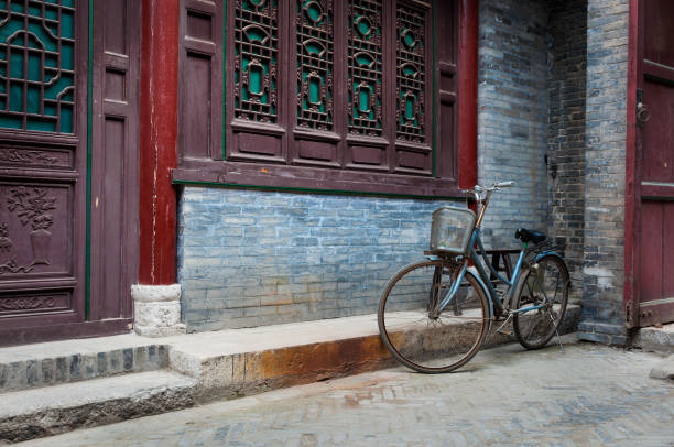A bicycle parked against an ornamented wall in the Great Mosque in the city of Xian, China A bicycle parked against an ornamented wall in the Great Mosque in the city of Xian, China, Asia grand mosque stock pictures, royalty-free photos & images