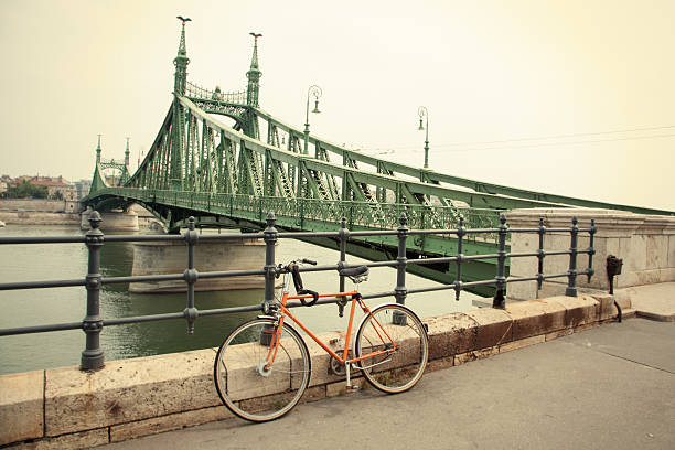 Bicycle parked by the Liberty bridge in Budapest, Hungary A bicycle parked by the Liberty bridge (Szabadság híd) in Budapest, Hungary. The bridge connects Buda and Pest across the River Danube and is located at the southern end of the city centre. liberty bridge budapest stock pictures, royalty-free photos & images