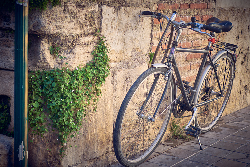 Bicycle parked by the wall on a street