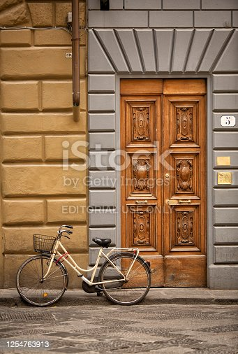 Florence, Italy, June 14, 2019: View of a bicycle parked on the kerb in front of an ornate timber door in Florence